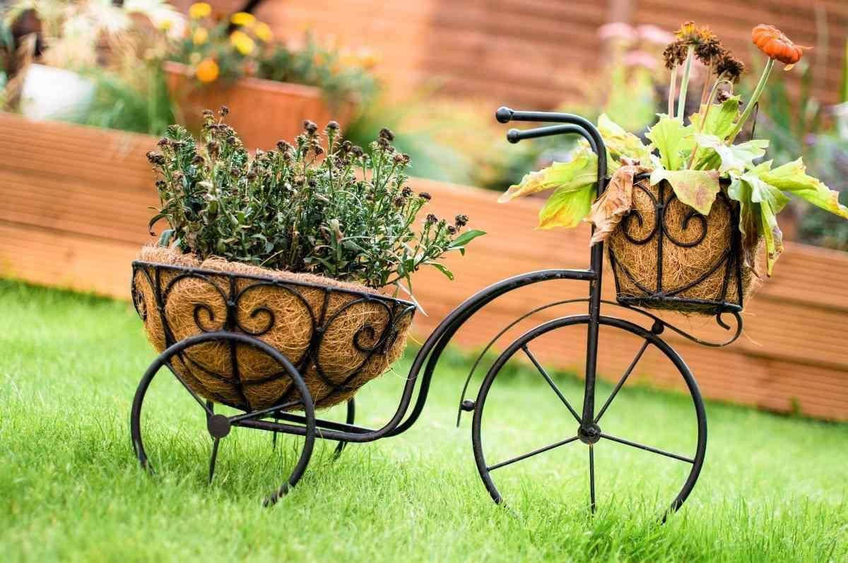 dekoratives fahrrad mit körbern für pflanzen im garten aufstellen