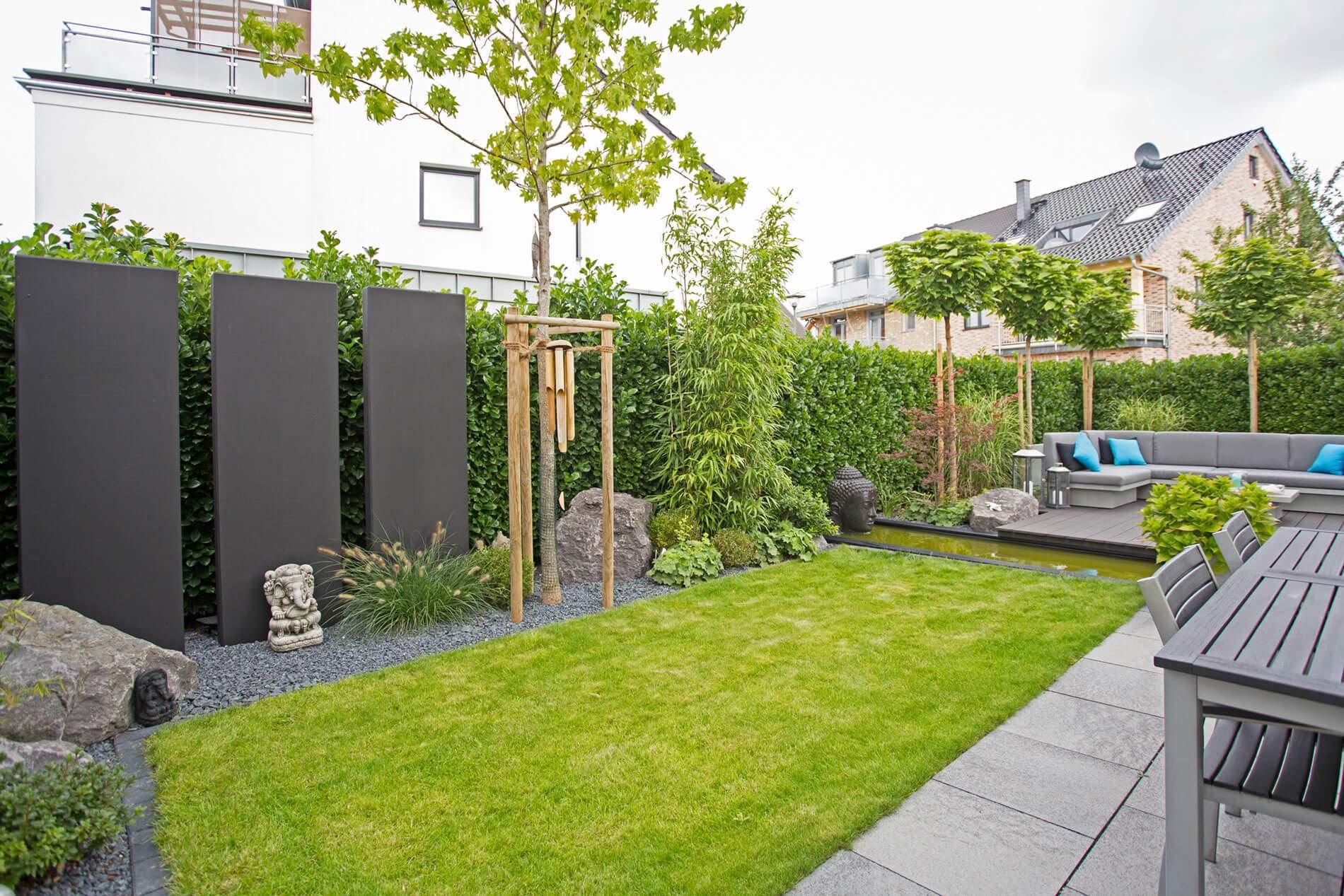 Lounge Ecke im Garten Sichtschutz aus Kirchlorbeer Hecke und monochromen Stelen