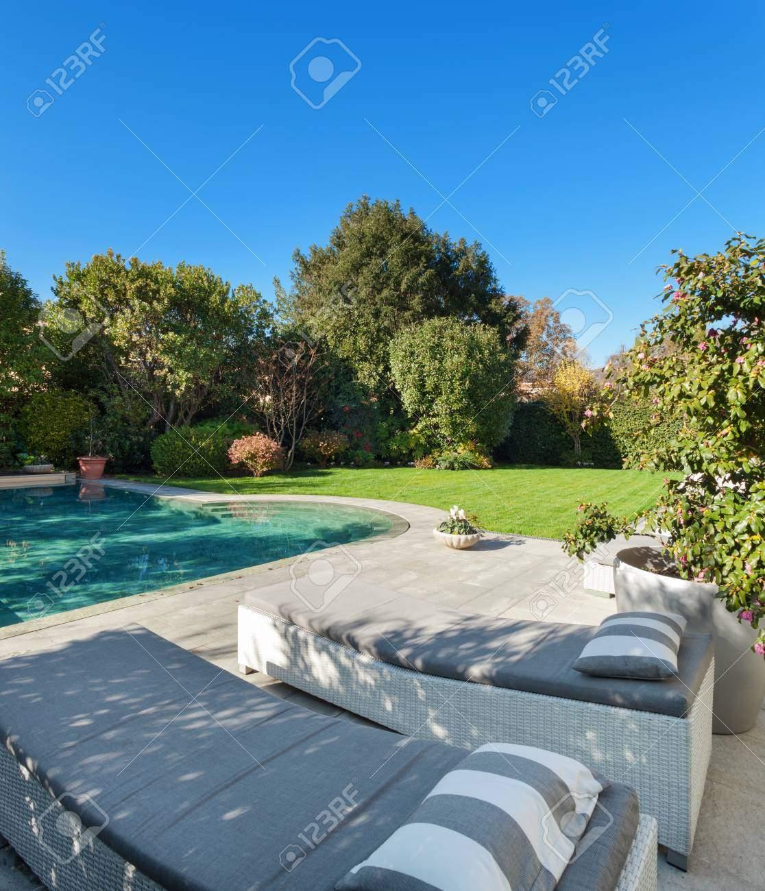 photo schöner garten mit pool zwei sonnenliegen
