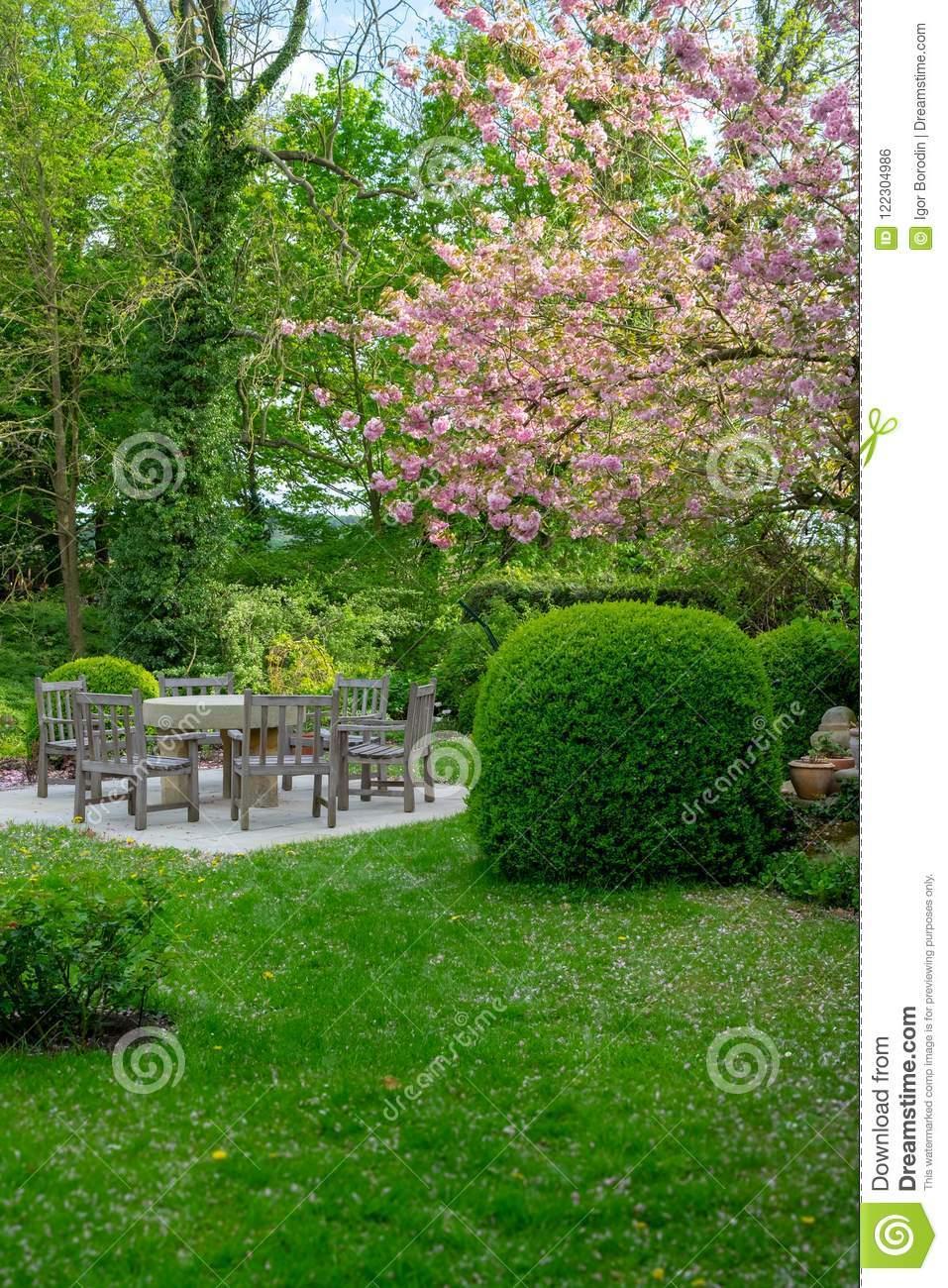 schöner garten mit tabelle und stühlen image